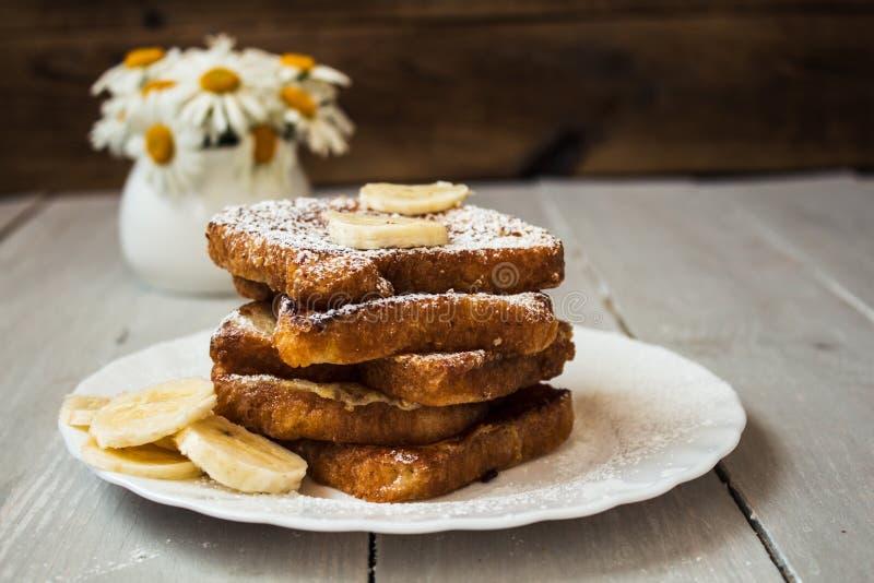 Pane inzuppato in latte/uova e zucchero e fritto in padella con il bannana su fondo di legno fotografie stock libere da diritti