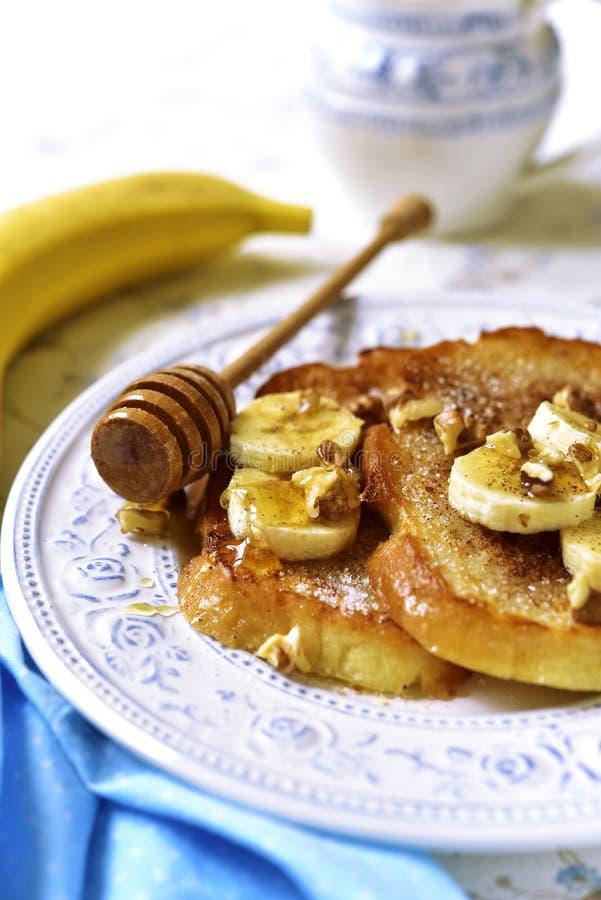 Pane inzuppato in latte/uova e zucchero e fritto in padella con la banana, le noci e la cannella immagini stock