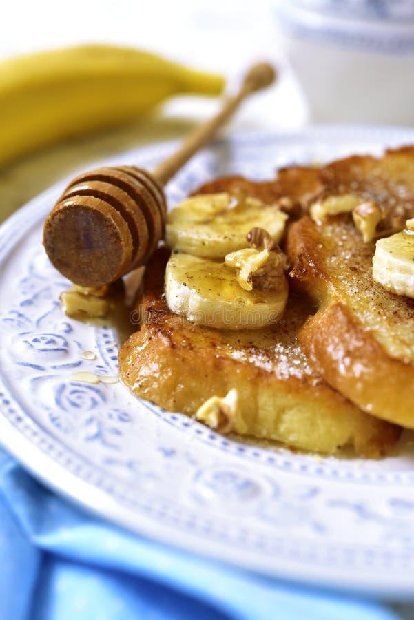 Pane inzuppato in latte/uova e zucchero e fritto in padella con la banana, le noci e la cannella immagini stock libere da diritti