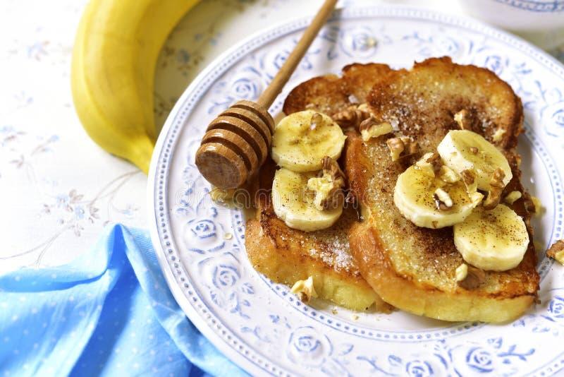 Pane inzuppato in latte/uova e zucchero e fritto in padella con la banana, le noci e la cannella fotografie stock