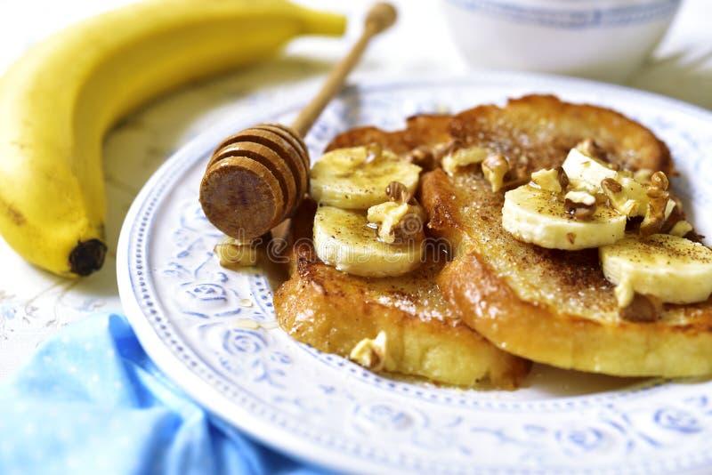 Pane inzuppato in latte/uova e zucchero e fritto in padella con la banana, le noci e la cannella fotografia stock