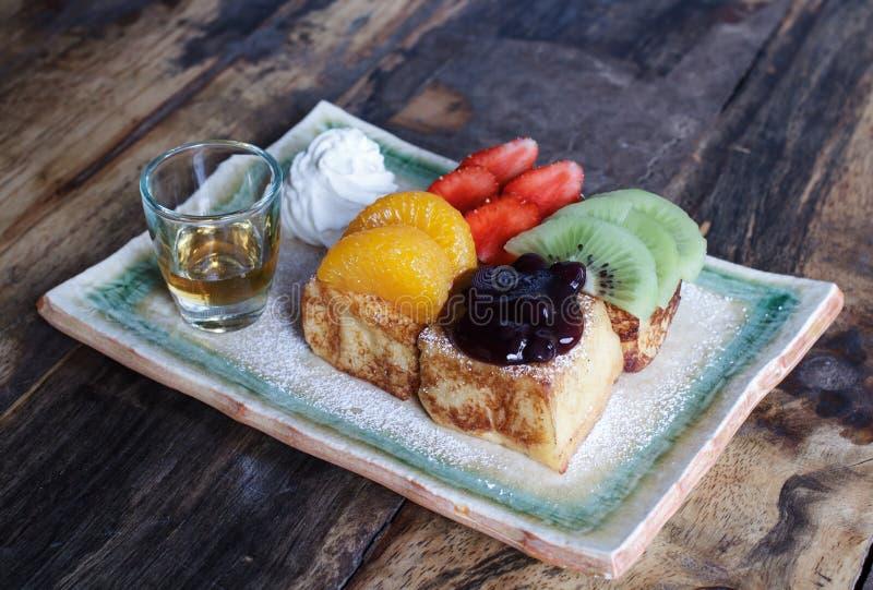 Pane inzuppato in latte/uova e zucchero e fritto in padella con la guarnizione della frutta e del miele immagini stock libere da diritti