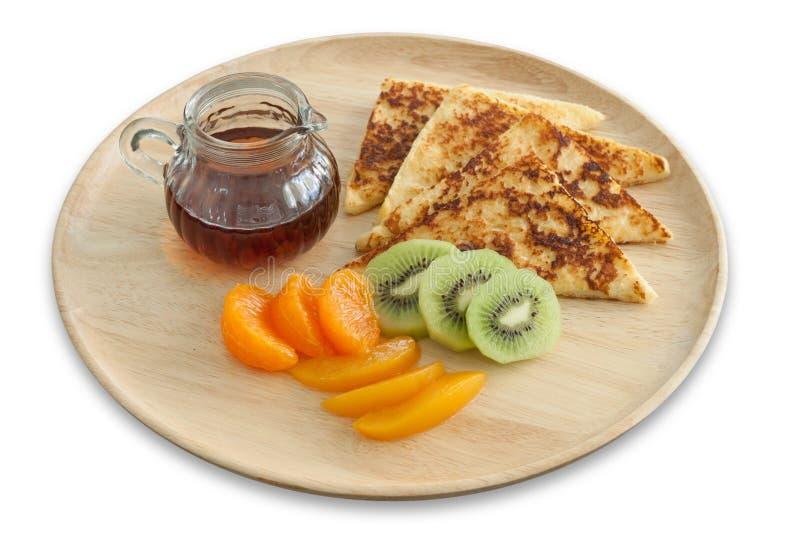 Pane inzuppato in latte/uova e zucchero e fritto in padella e frutta fresca con miele sul piatto di legno per la prima colazione immagini stock