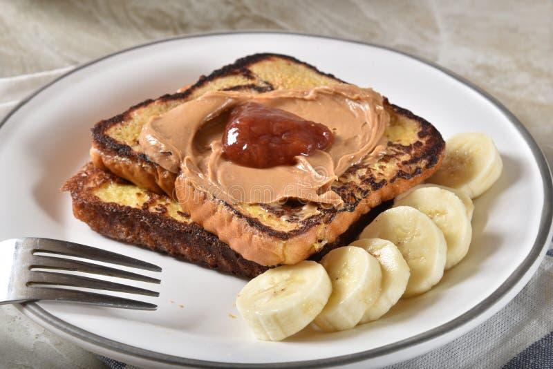 Pane inzuppato in latte/uova e zucchero e fritto in padella con burro di arachidi, gelatina e la banana immagine stock libera da diritti