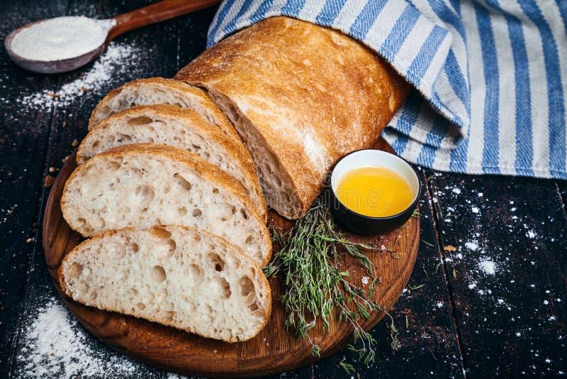 Pane italiano casalingo affettato di ciabatta con olio d'oliva su fondo scuro Ciabatta, erbe, olio d'oliva, farina Chiuda sulla v fotografia stock libera da diritti