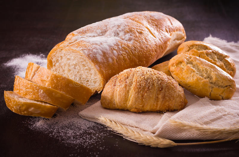 Pane italiano e l'altro alimento al forno in tavola di legno immagini stock libere da diritti