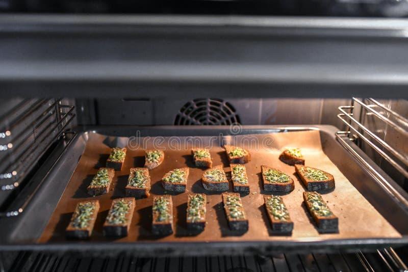 Pane nero con formaggio nel forno Pane arrostito con formaggio e le spezie, cucinati nel forno su un vassoio nero, prima colazion fotografia stock