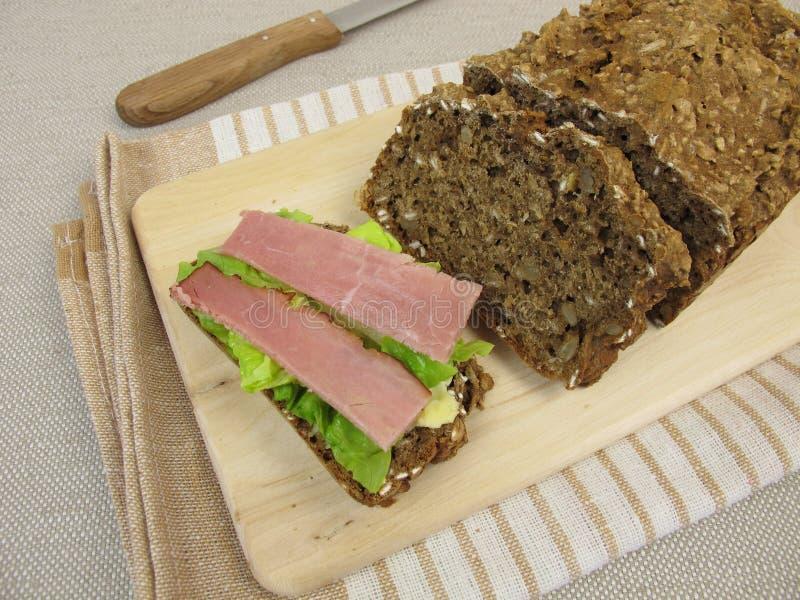 Pane nero con la foglia della lattuga e del prosciutto immagine stock