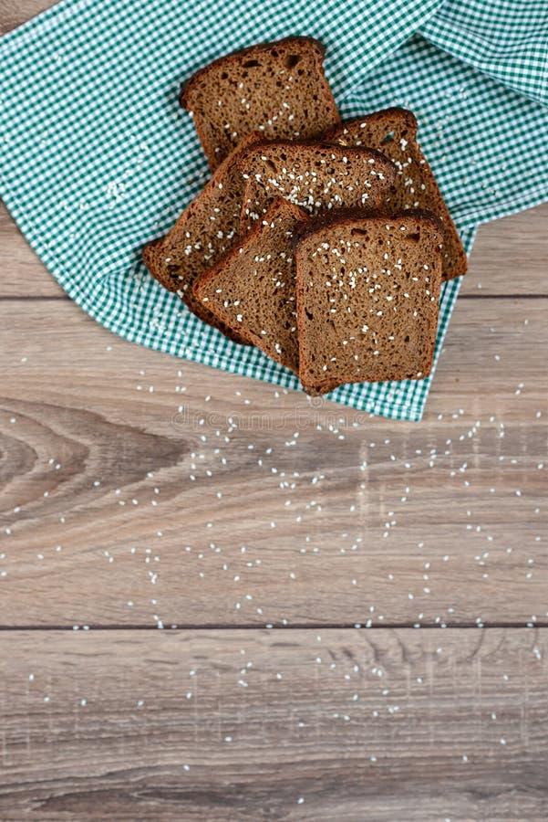 Pane nero, panno, fondo di legno fotografie stock