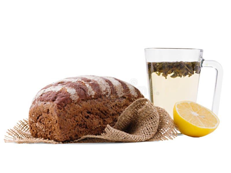Pane nero, sul panno di tela da imballaggio, accanto ad una tazza trasparente con tè ed il limone mezzo fotografie stock