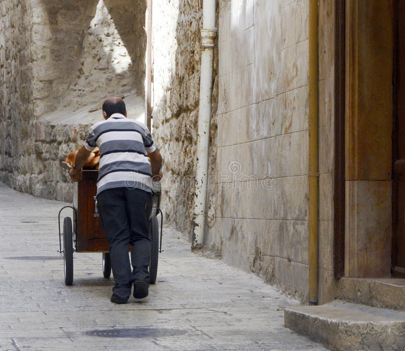 Pane o vendedor que empurra seu carro em um corredor de Christian Quarter, Jerusalém, Israel fotos de stock royalty free
