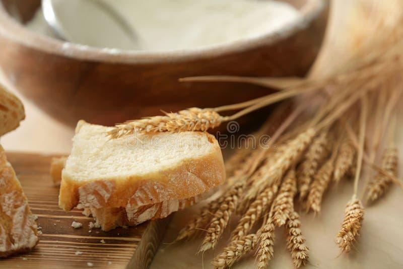Pane saporito, bordo di legno e spighette del grano fotografie stock
