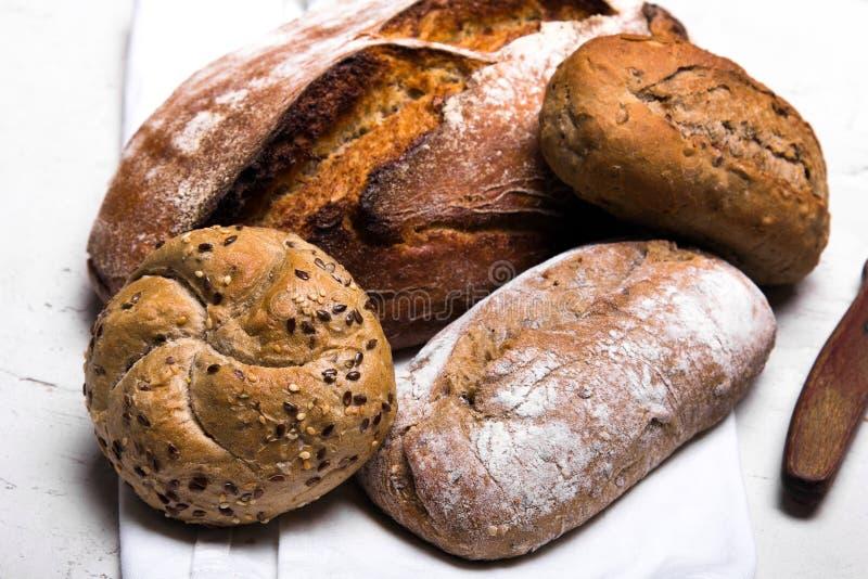 Pane scuro e panini saporiti su fondo bianco, fotografie stock libere da diritti