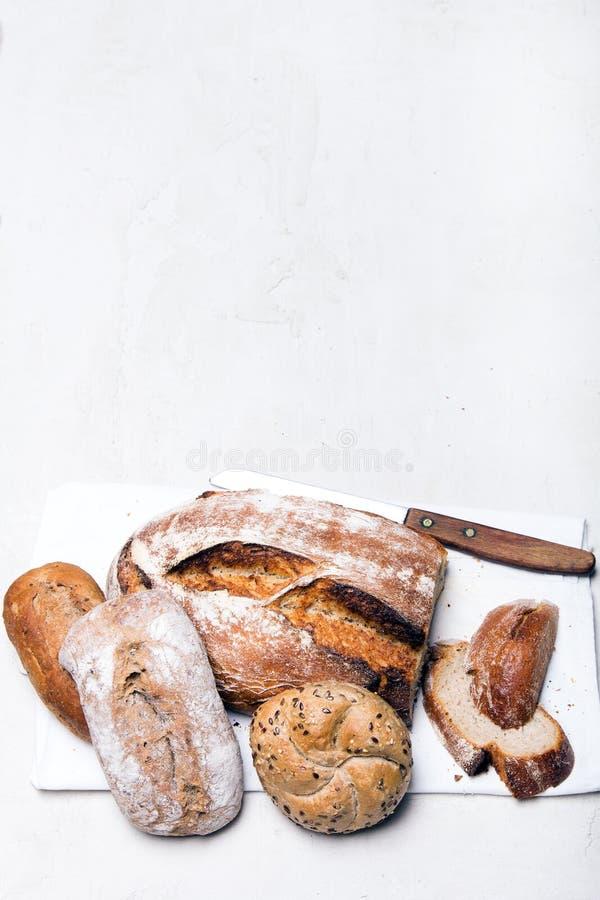 Pane scuro e panini saporiti su fondo bianco, spazio della copia fotografie stock