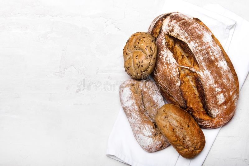Pane scuro e panini saporiti su fondo bianco, spazio della copia fotografia stock libera da diritti