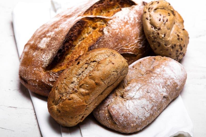 Pane scuro e panini saporiti su fondo bianco, spazio della copia fotografie stock libere da diritti