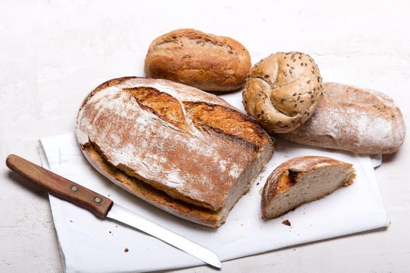 Pane scuro e panini saporiti su fondo bianco, spazio della copia immagine stock