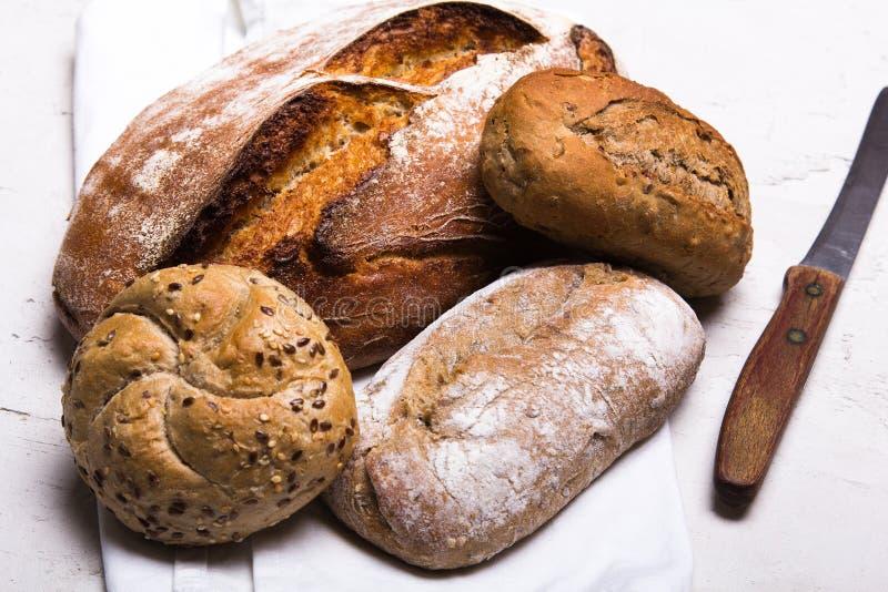 Pane scuro e panini saporiti su fondo bianco, spazio della copia immagini stock