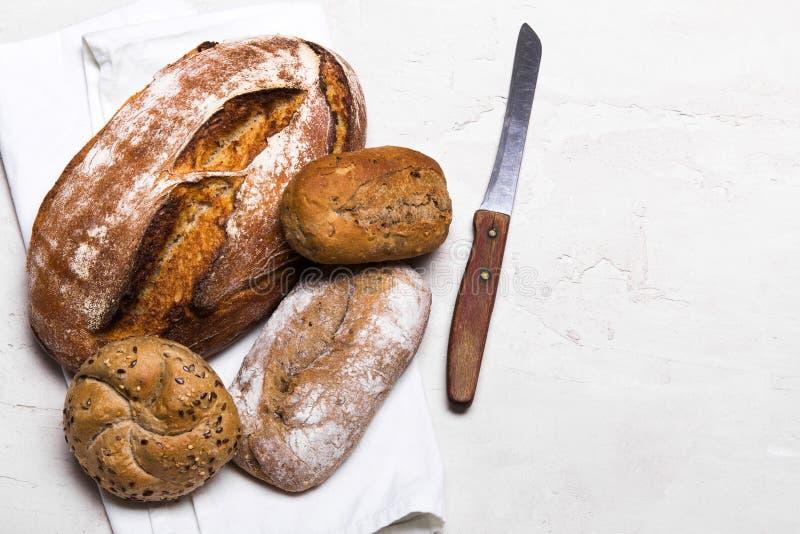 Pane scuro e panini saporiti su fondo bianco, spazio della copia immagini stock libere da diritti