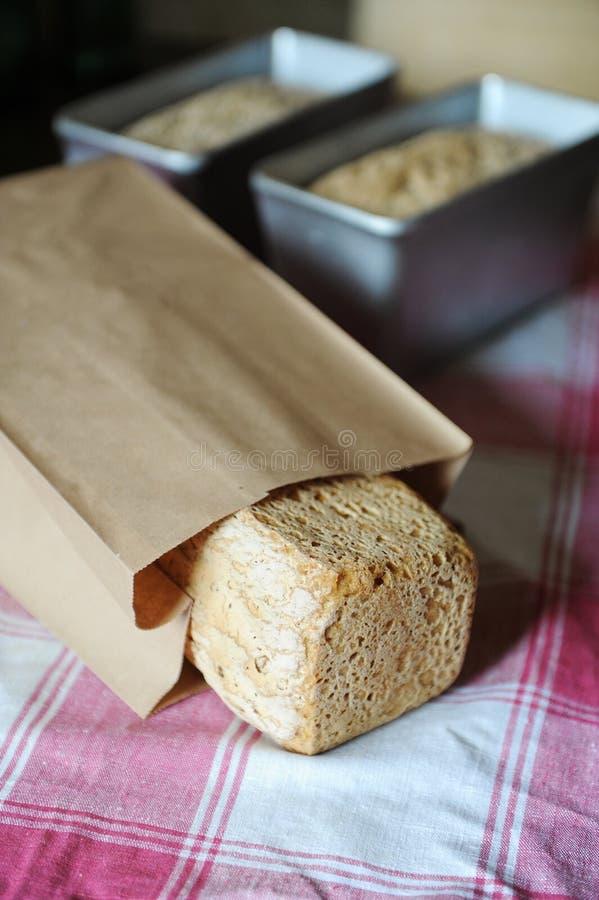 Pane su un fermento della segale senza lievito in un sacco di carta su una tovaglia a quadretti Pagnotte nelle forme di cottura n fotografia stock