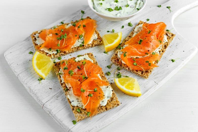 Pane tostato casalingo del pane croccante con il salmone affumicato, il formaggio fuso e l'insalata del crescione sul bordo di le immagini stock