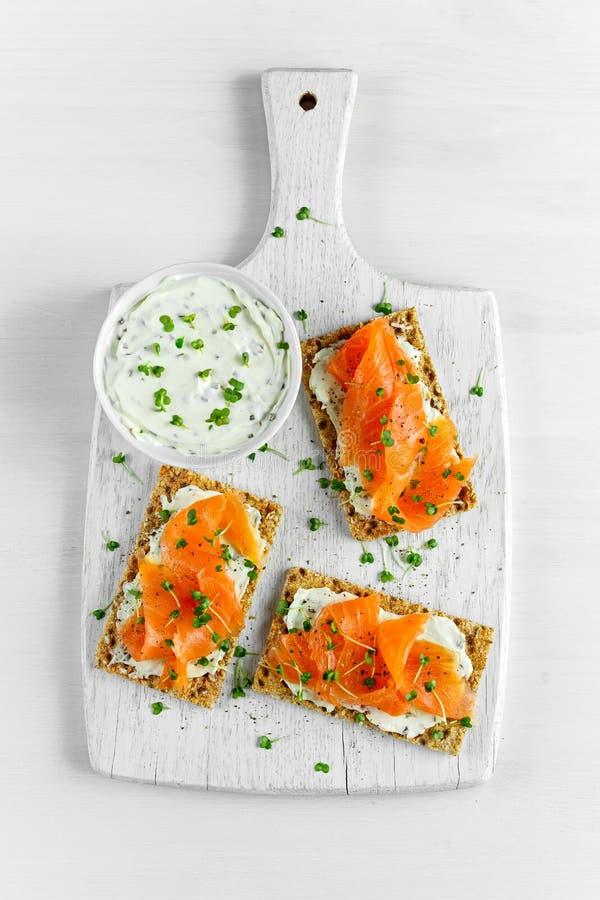 Pane tostato casalingo del pane croccante con il salmone affumicato, il formaggio fuso e l'insalata del crescione sul fondo bianc immagine stock