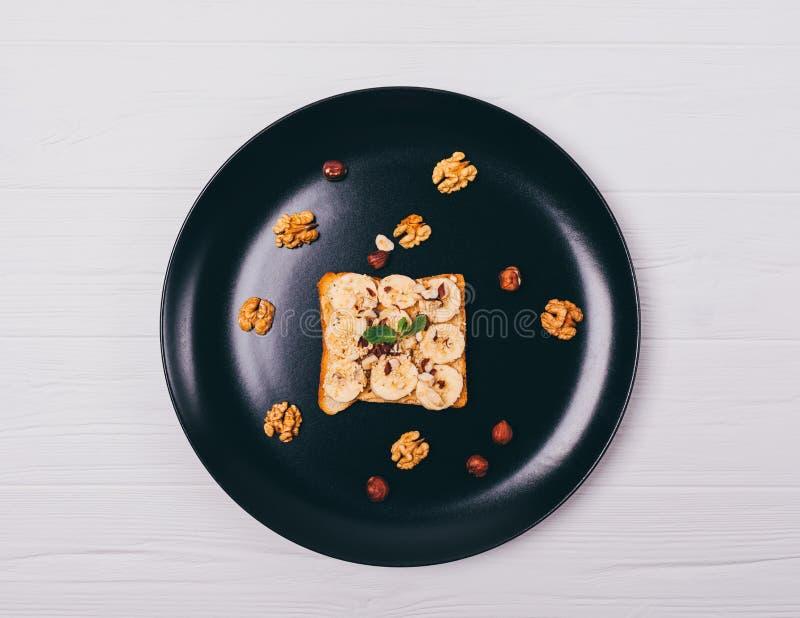Pane tostato con burro di arachidi, le banane ed i dadi su un piatto fotografia stock