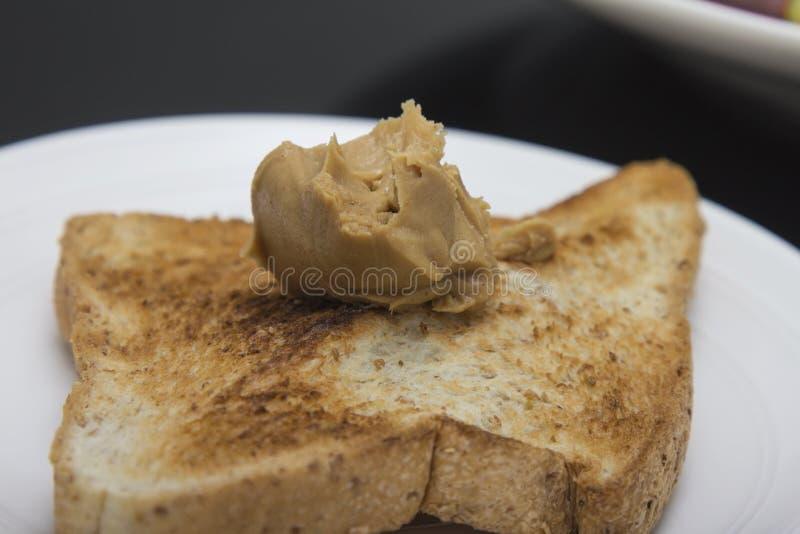 Pane tostato con il mestolo di burro di arachidi fotografia stock libera da diritti