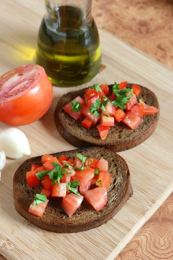 Pane tostato con il pomodoro e l'olio tagliati immagini stock libere da diritti