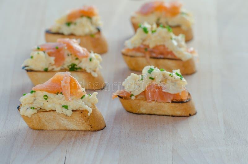 Pane tostato con il salmone affumicato con le uova rimescolate fotografie stock libere da diritti