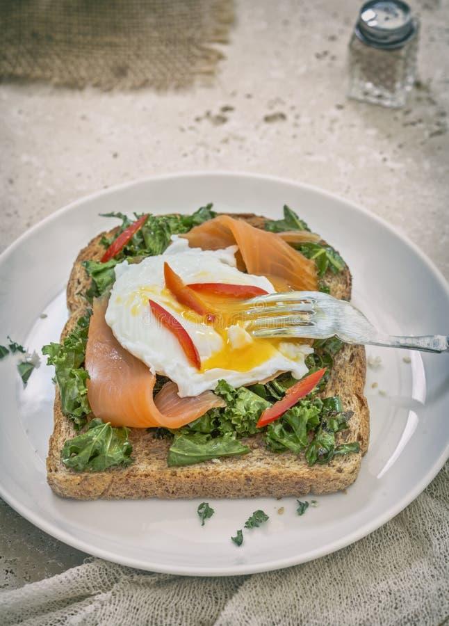 Pane tostato con il salmone affumicato, l'uovo affogato ed il cavolo verde fotografie stock