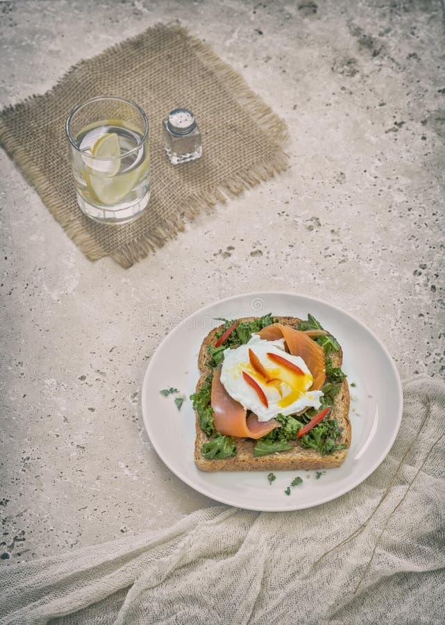 Pane tostato con il salmone affumicato, l'uovo affogato ed il cavolo verde immagini stock libere da diritti