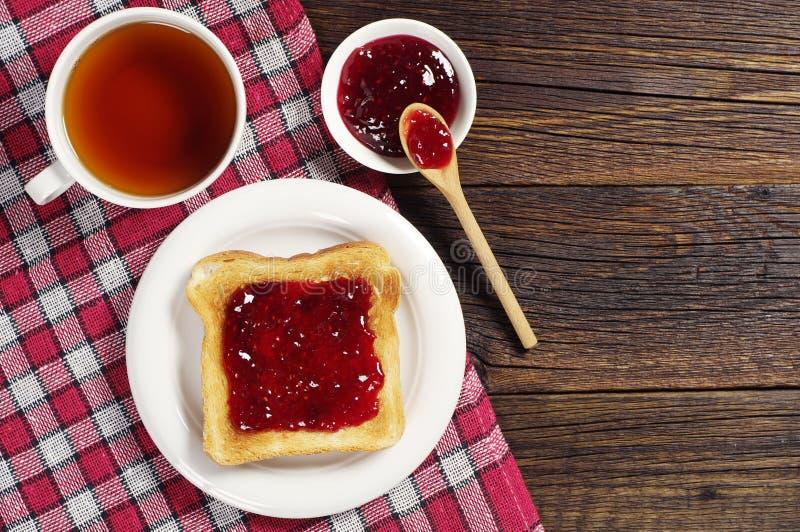 Pane tostato con inceppamento e tè immagine stock