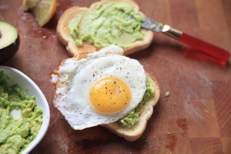 Pane tostato con l'avocado schiacciato e l'uovo fritto immagini stock libere da diritti