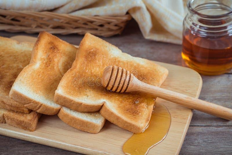 Pane tostato con miele sul piatto di legno fotografie stock