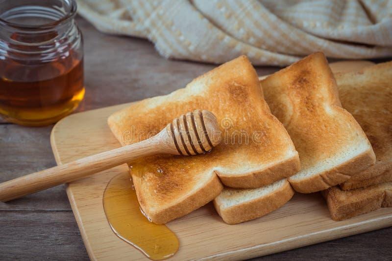 Pane tostato con miele sul piatto di legno immagine stock