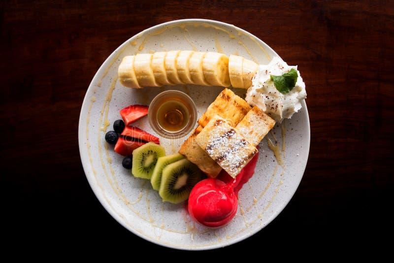 Pane tostato del miele che completa dalla fragola del gelato con frutta fotografia stock