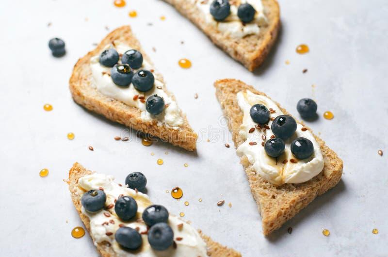 Pane tostato del mirtillo, seme di lino, del bacca del formaggio cremoso e dessert dello sciroppo d'acero, pasto organico sano fotografia stock