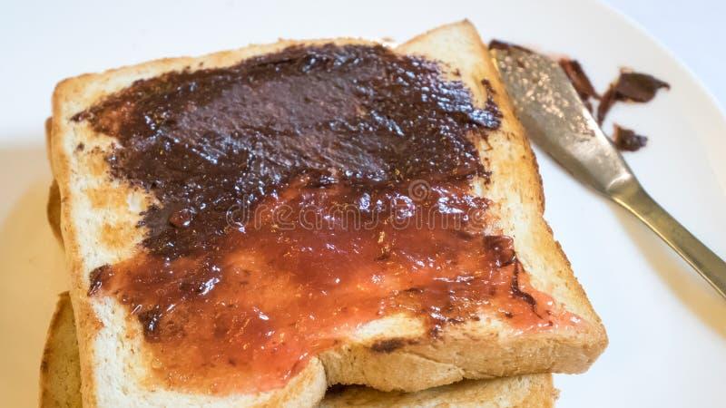 Pane tostato del pane ed inceppamento di fragola saporiti con la diffusione del cioccolato immagini stock libere da diritti