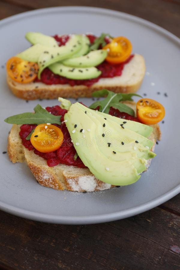 Pane tostato del vegano con i pomodori e la barbabietola della rucola dell'avocado fotografia stock