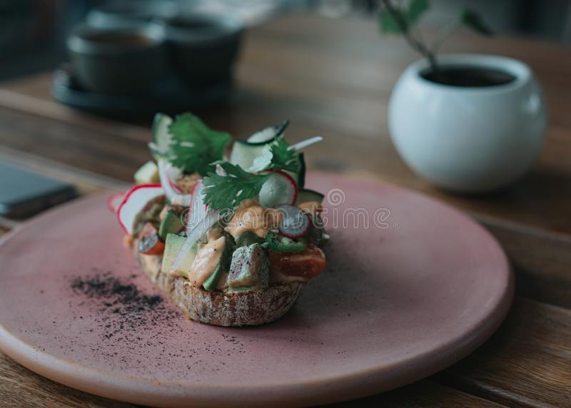 Pane tostato delizioso dell'avocado con pane artigianale su un piatto rosa immagini stock libere da diritti