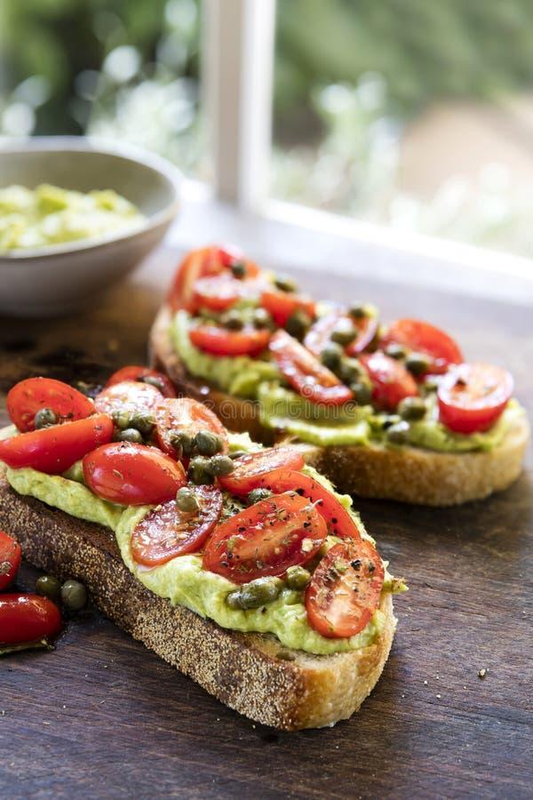 Pane tostato dell'avocado con la salsa del cappero e di Cherry Tomato fotografie stock