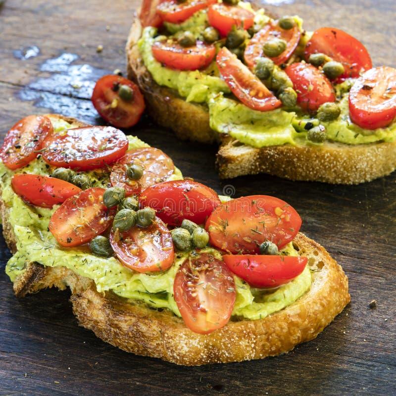Pane tostato dell'avocado con la salsa del cappero e di Cherry Tomato fotografia stock