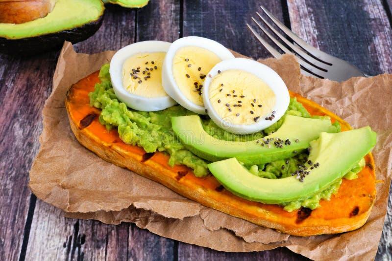 Pane tostato della patata dolce con l'avocado, le uova ed i semi di chia, scena della tavola immagini stock libere da diritti