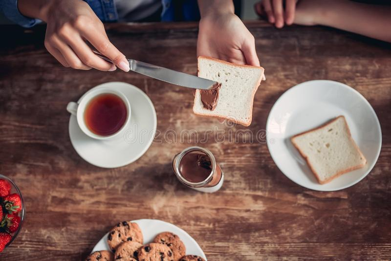 Pane tostato di diffusione della donna con la pasta del cioccolato immagini stock libere da diritti