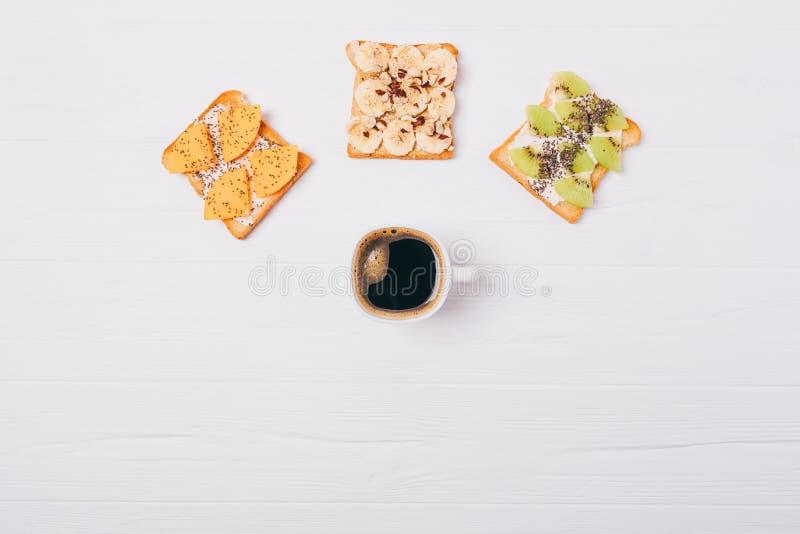 Pane tostato differente della frutta tre e della tazza di caffè, vista superiore Composizione posta piana della prima colazione s fotografia stock libera da diritti