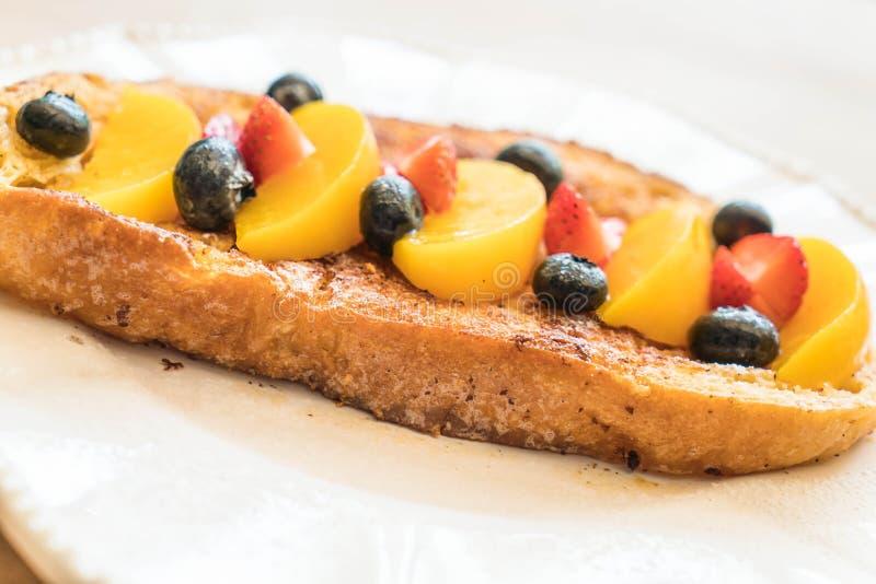 pane tostato francese con la pesca, la fragola ed i mirtilli immagine stock