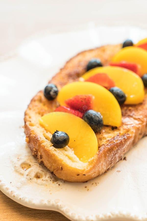 pane tostato francese con la pesca, la fragola ed i mirtilli fotografia stock