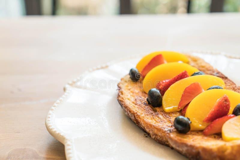 pane tostato francese con la pesca, la fragola ed i mirtilli immagini stock