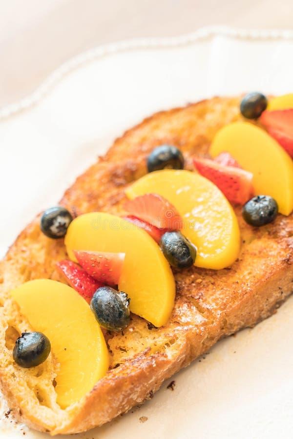 pane tostato francese con la pesca, la fragola ed i mirtilli fotografie stock libere da diritti